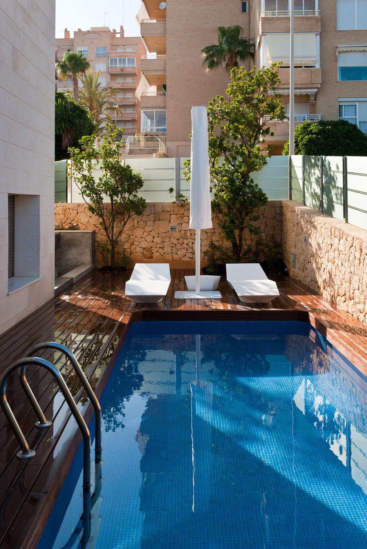 diseno de jardin pequeno con tarima de madera y piscina